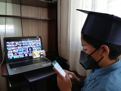 Bachiller 2020 pasando clases online desde la comodidad de su casa, pero a la vez distraído por los aparatos que tiene a la mano.